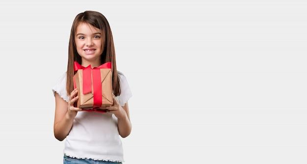 Corpo inteiro menina feliz e sorridente, segurando um belo presente, animado e cheio, comemorando um aniversário ou um evento em destaque