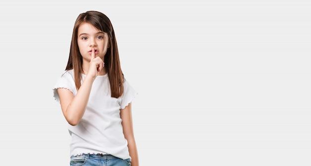 Corpo inteiro menina mantendo um segredo ou pedindo silêncio, cara séria, conceito de obediência