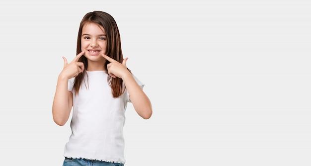 Corpo inteiro menina sorri, apontando a boca, conceito de dentes perfeitos, dentes brancos, tem uma atitude alegre e jovial