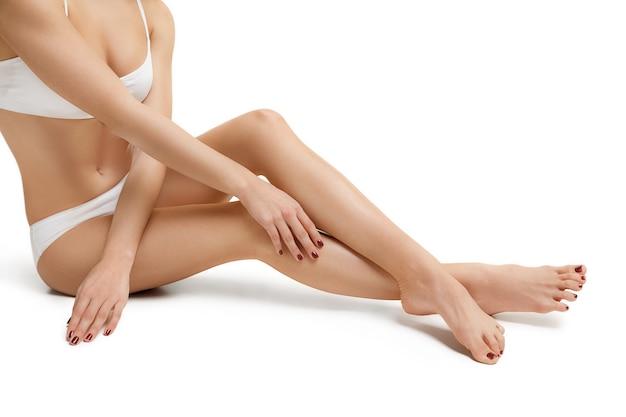 Corpo jovem tonificado e magro perfeito da garota ou mulher em forma no estúdio. os esportes de dieta de fitness