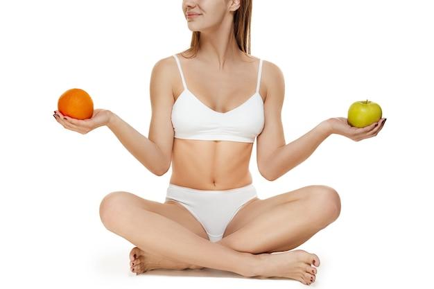 Corpo jovem tonificado magro perfeito da menina ou ajuste mulher sentada no estúdio com frutas. o conceito de fitness, dieta, esportes, cirurgia plástica e cosmetologia estética. a imagem não é retocada na forma do corpo