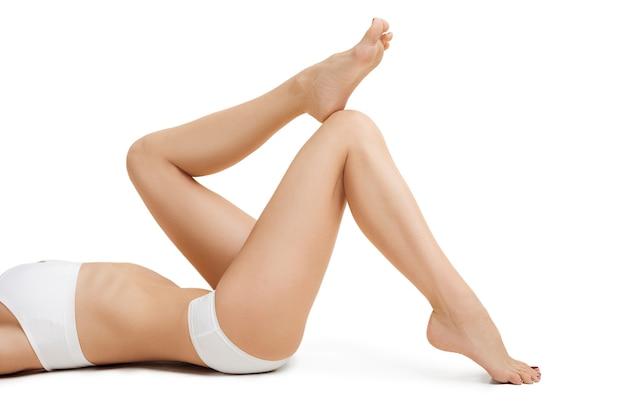 Corpo jovem tonificado magro perfeito da menina ou mulher em forma no estúdio. o conceito de fitness, dieta, esportes, cirurgia plástica e cosmetologia estética. a imagem não é retocada na forma do corpo