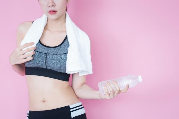 Corpo magro da mulher asiática saudável do esporte com toalha e garrafa do exercício e do exercício da água.
