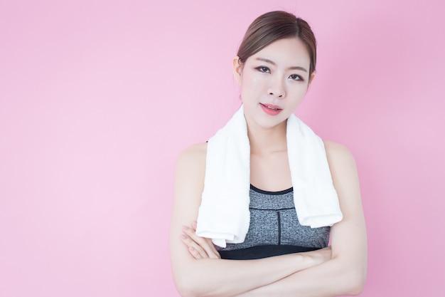 Corpo magro da mulher asiática saudável do esporte com toalha e sutiã dos esportes, exercício e exercício.