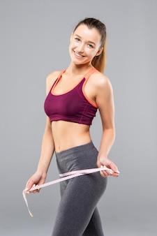 Corpo magro de mulher bronzeada com fita métrica