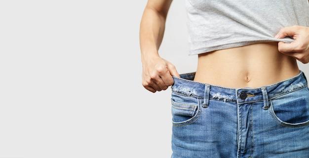 Corpo magro de mulher com calças jeans largas, corpo leve com roupas soltas