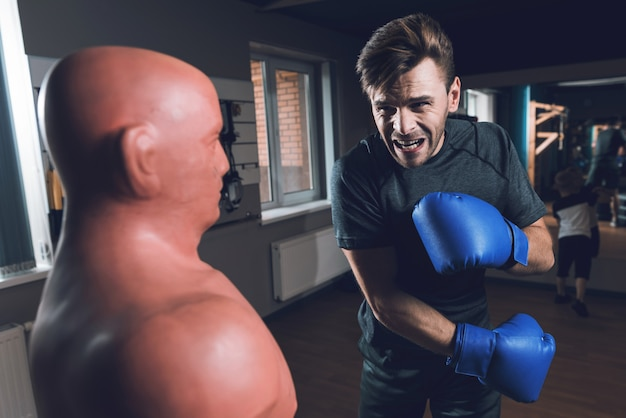 Corpo oponente saco e homem em luvas de boxe.