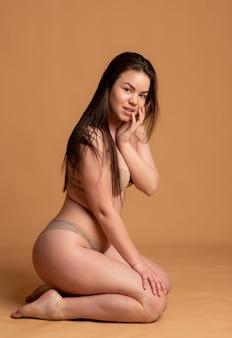 Corpo positivo. uma garota de cueca bege posa em um fundo rosa. foto de alta qualidade