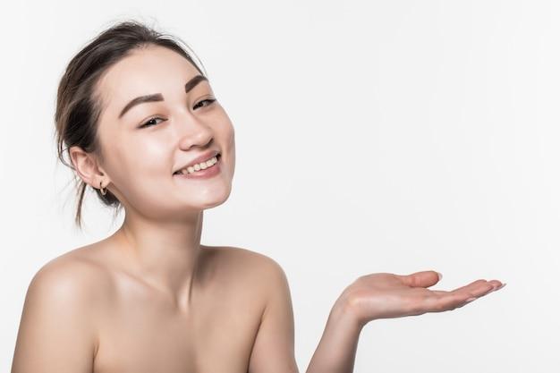 Corpo skincare cuidados beleza asiática mulher mostrando o produto no lado com a mão aberta, apresentando e exibindo isolado na parede branca.