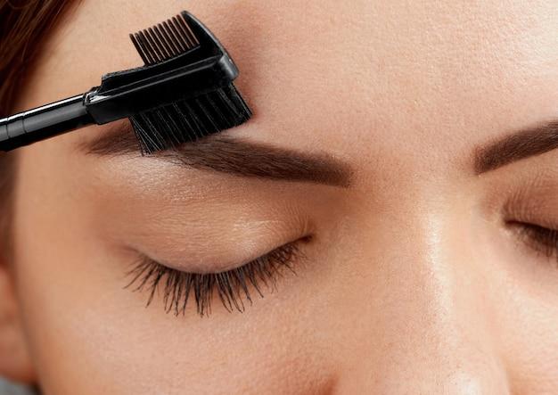 Correção de sobrancelha. close da mulher jovem e bonita com uma maquiagem perfeita e longos cílios, arrancando as sobrancelhas.