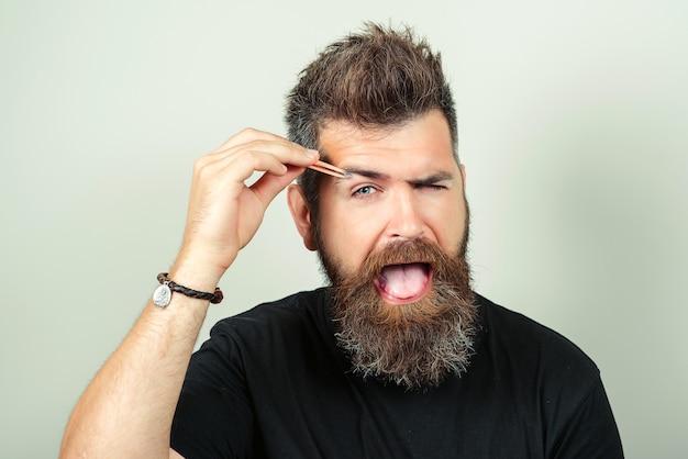 Correção de sobrancelha. noivos no banheiro em casa. sobrancelhas arrancando masculinos bonitos enquanto no salão de beleza.