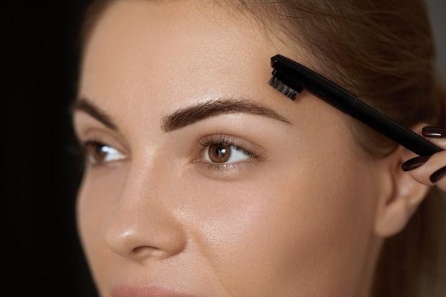 Correção de sobrancelhas. forma. mulher jovem e bonita com sobrancelhas e cílios naturais perfeitos.