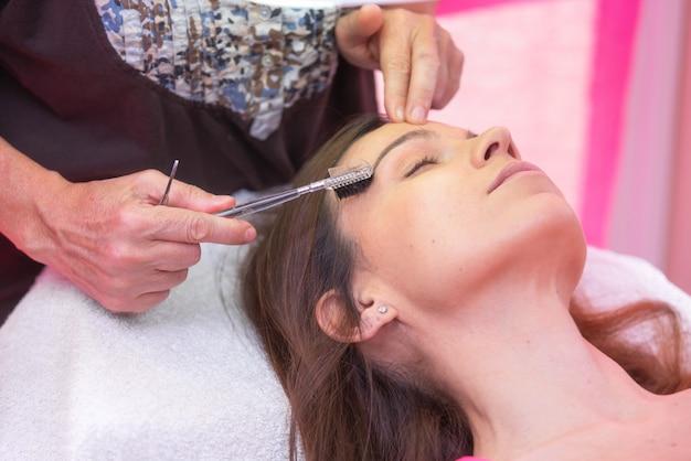 Correção profissional da sobrancelha do havind da jovem mulher no salão de beleza dos termas.
