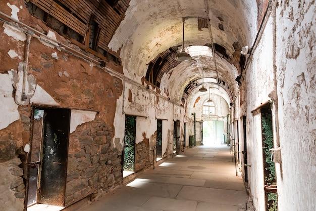 Corredor antigo da prisão com celas abertas.