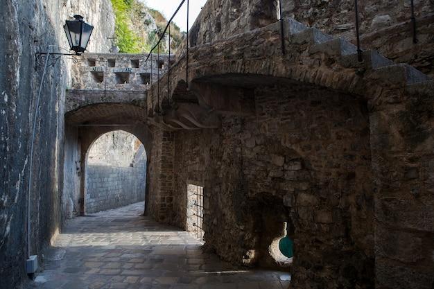 Corredor antigo de pedra com janela redonda na cidade velha