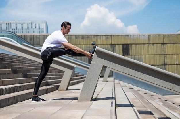 Corredor atlético fazendo exercícios de alongamento se preparando para o treino matinal no parque