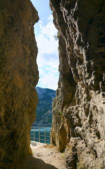 Corredor através da rocha e vista na baía do mar (reserva