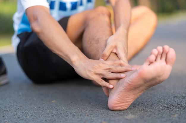 Corredor com dor no tornozelo e problema após a corrida e exercício fora da manhã