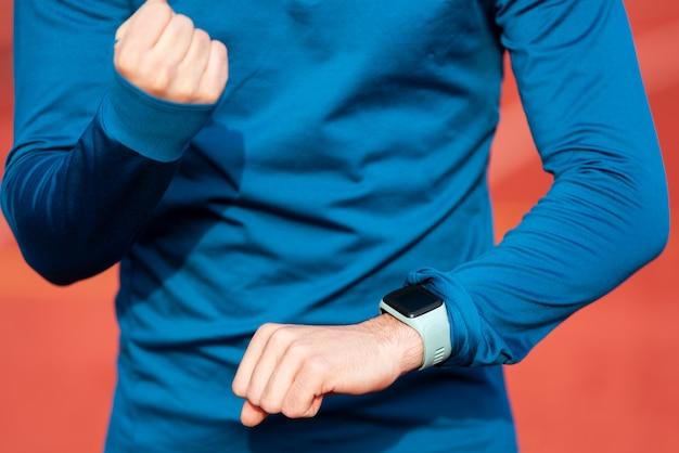 Corredor com sucesso que olha o relógio esperto do monitor da frequência cardíaca, fim acima.