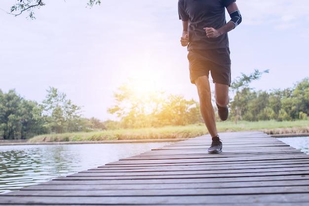 Corredor correndo na ponte de madeira, worm up e exercício