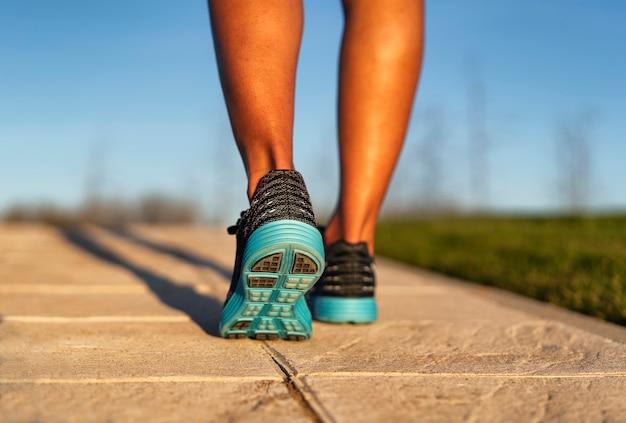 Corredor da jovem mulher que começa uma sessão de treinamento do outwork, umas sapatilhas azuis e pretas. fitness e estilo de vida saudável