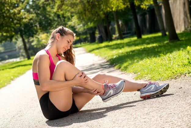Corredor da jovem mulher que toca o pé na dor ao ar livre