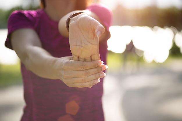 Corredor da mulher que estica a mão antes de correr no parque.