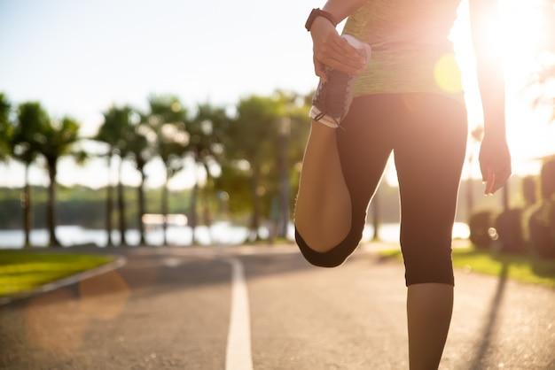 Corredor da mulher que estica os pés antes da corrida no parque. conceito de exercício ao ar livre.