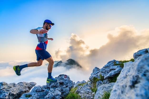 Corredor da ultramaratona nas montanhas treinando ao pôr do sol