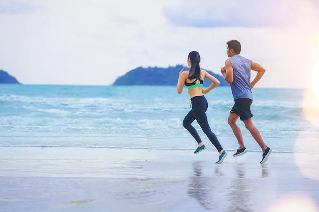 Corredor de casais correndo na praia com o por do sol.