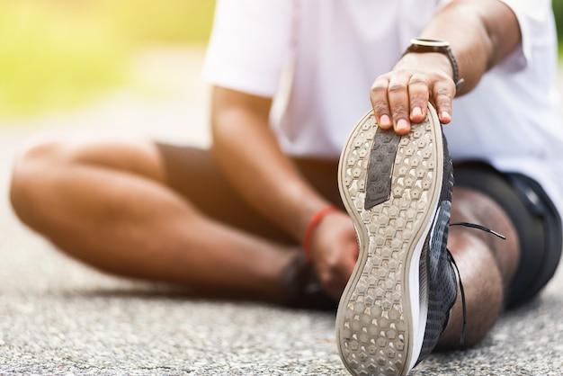 Corredor de esporte homem negro usar relógio ele sentado puxar os dedos dos pés, esticando as pernas e joelho