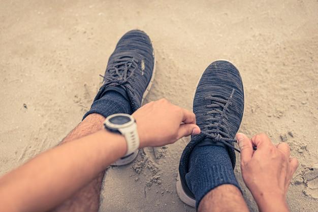Corredor de homem, amarrando o cadarço pronto para correr na praia