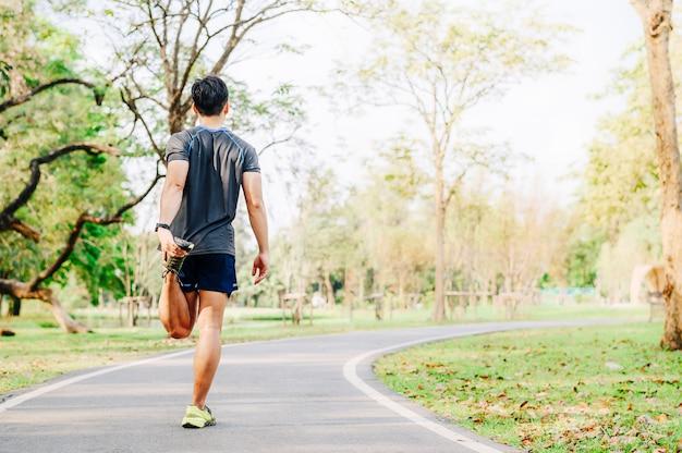 Corredor de homem fazendo exercícios de alongamento