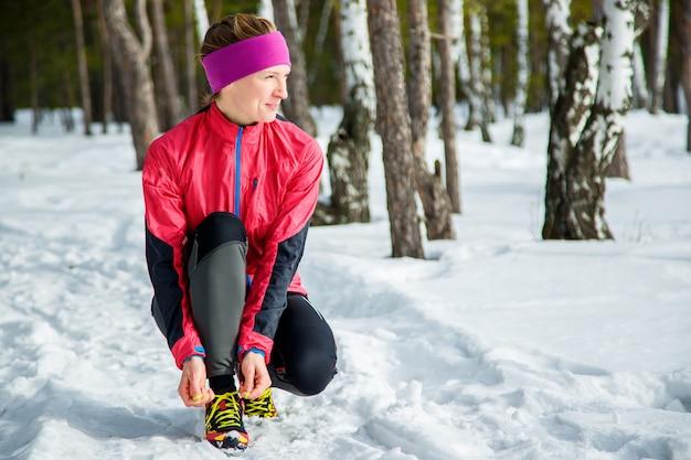 Corredor de inverno se preparando correndo amarrar cadarços de sapato