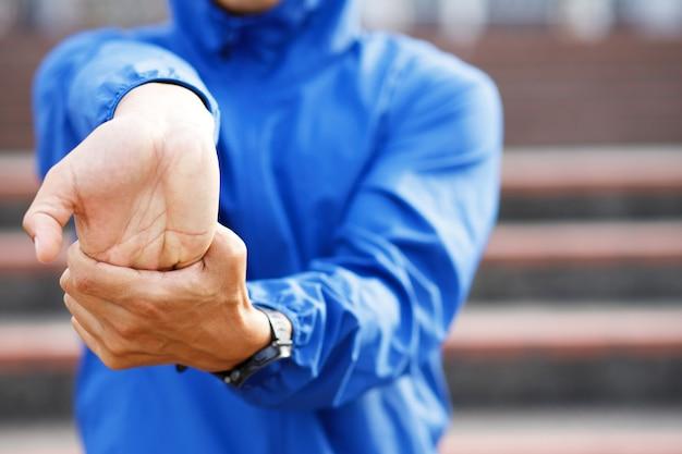 Corredor de jovem alongamento para aquecimento antes de correr ou malhar na estrada. exercício de atleta de atletismo. conceito de estilo de vida saudável e fitness