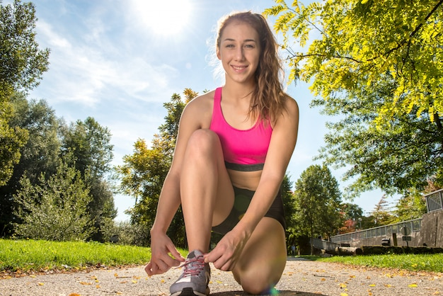 Corredor de jovem amarrando os sapatos dela se preparando para uma corrida