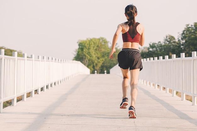 Corredor de jovem correndo na estrada em execução no parque da cidade