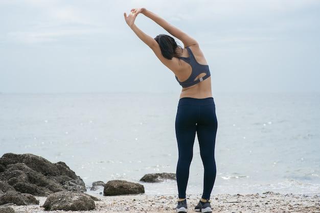 Corredor de jovem mulher asiática, estendendo-se na praia