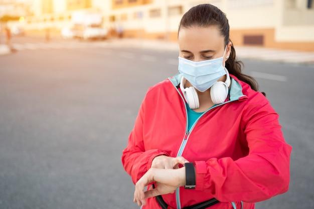 Corredor de jovem mulher usando máscara médica e fone de ouvido olhando para o relógio de esporte e verificar o progresso no relógio inteligente