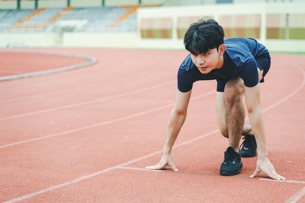 Corredor de jovem no ponto de partida na pista de corrida