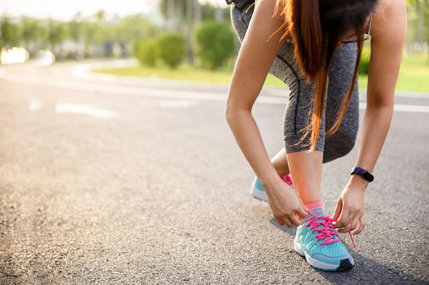 Corredor de mulher amarrando o tênis antes de correr para o exercício de manhã.