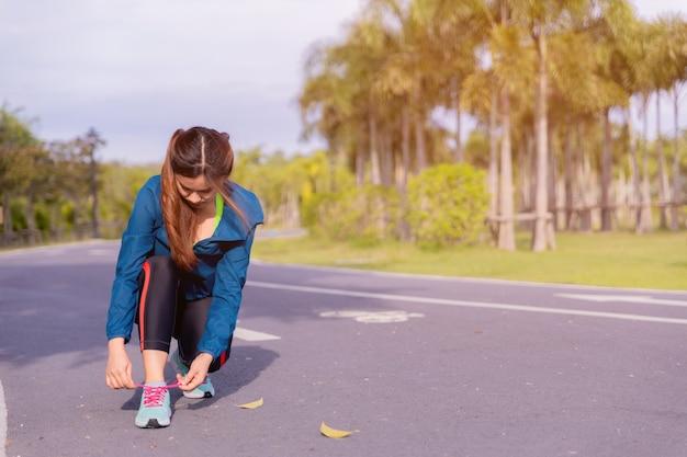 Corredor de mulher amarrando o tênis antes de executar para o exercício da manhã