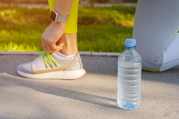 Corredor de mulher, amarrando os cadarços dos sapatos, preparando-se para uma corrida matinal