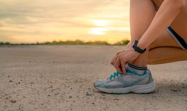 Corredor de mulher amarrando sapatos esporte e se preparando para correr no parque de manhã. exercício cardio feminino asiático para vida saudável. jogging ao ar livre. .
