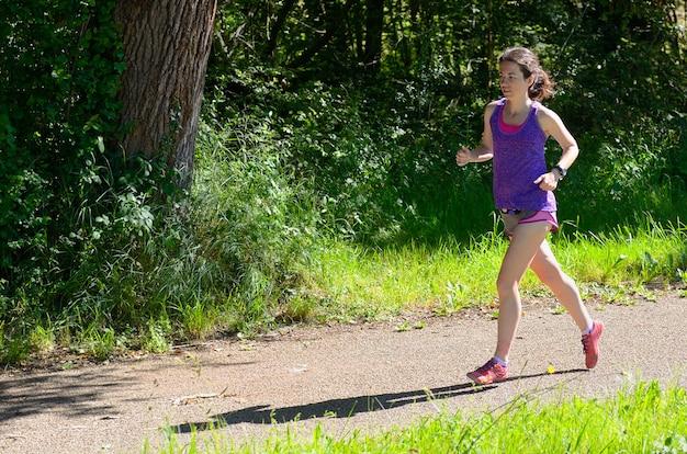 Corredor de mulher ativa, movimentando-se perto do rio canal, correndo ao ar livre, esporte, fitness e conceito de estilo de vida saudável