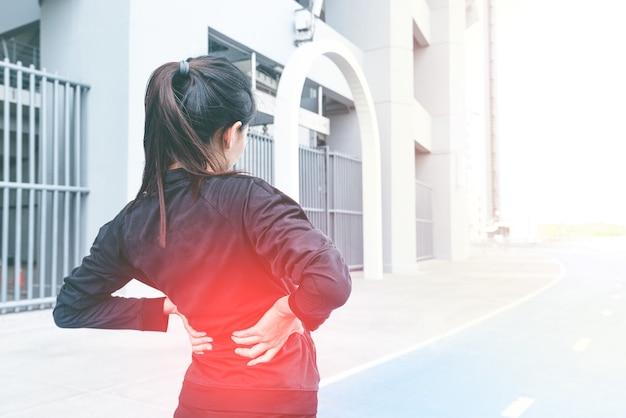 Corredor de mulher atleta com lesão de dor nas costas.