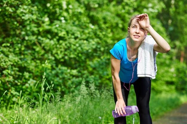 Corredor de mulher cansada descansando depois de correr duro na estrada na floresta, dobrando-se para a frente, descansando os cotovelos sobre os joelhos.