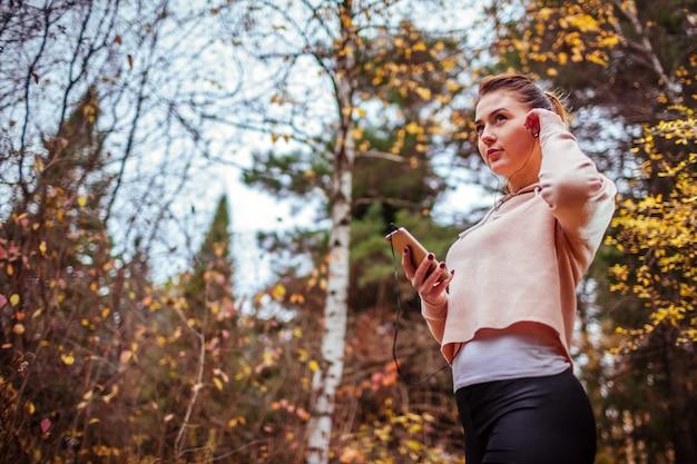 Corredor de mulher coloca seus fones de ouvido para ouvir a música