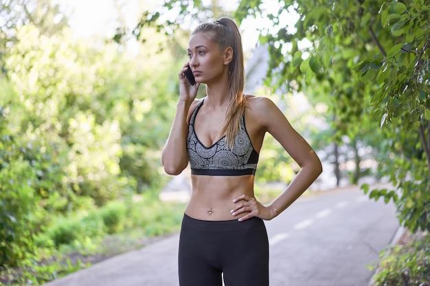 Corredor de mulher em pé antes de exercer o parque de verão falando ao telefone.