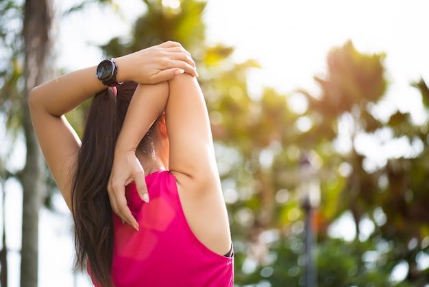 Corredor de mulher, esticando o braço no parque.